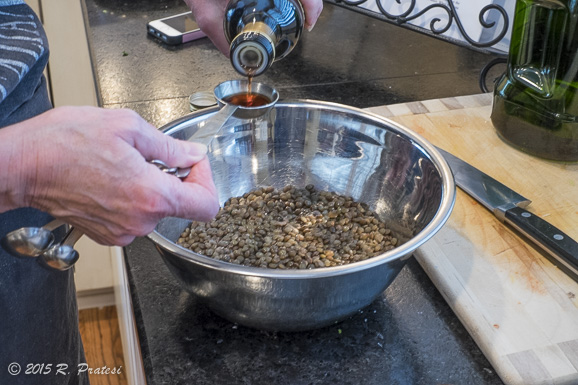 Seasoning the lentils with red wine vinegar and olive oil